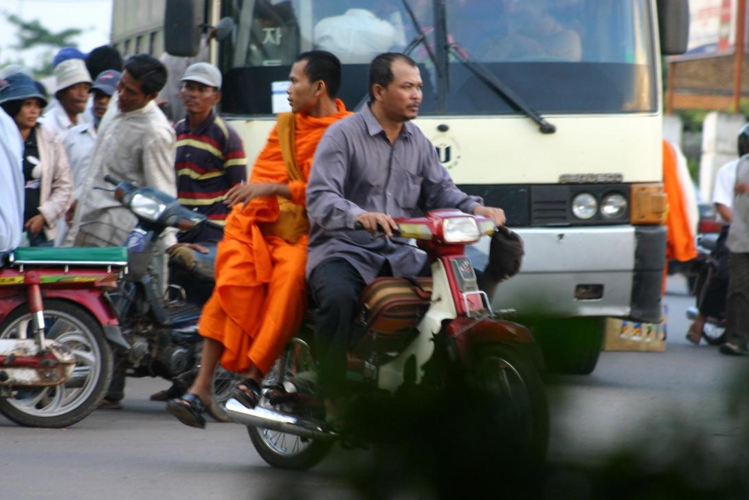 Buddhist monk driven by a moto taxi in Cambodia